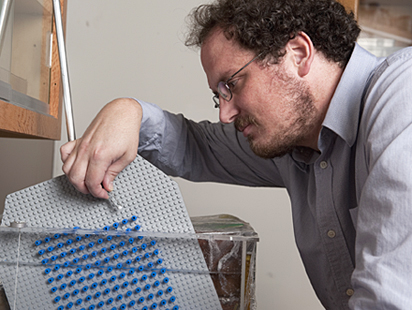 German Drazer, assistant professsor of chemical and biomolecular engineering, prepares to use a LEGO board to study the way particles behave in a microfuidic device. - Photo by Will Kirk.